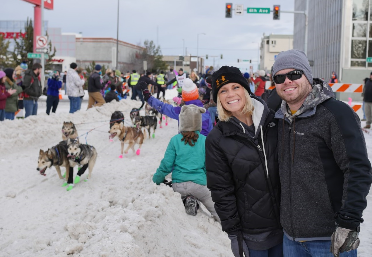 happy Alaska couple with iditarod sled team