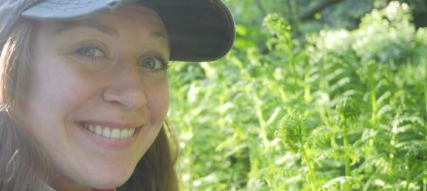 Ashley Taborsky smiling with fiddleheads
