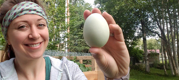 young woman holding colored chicken egg